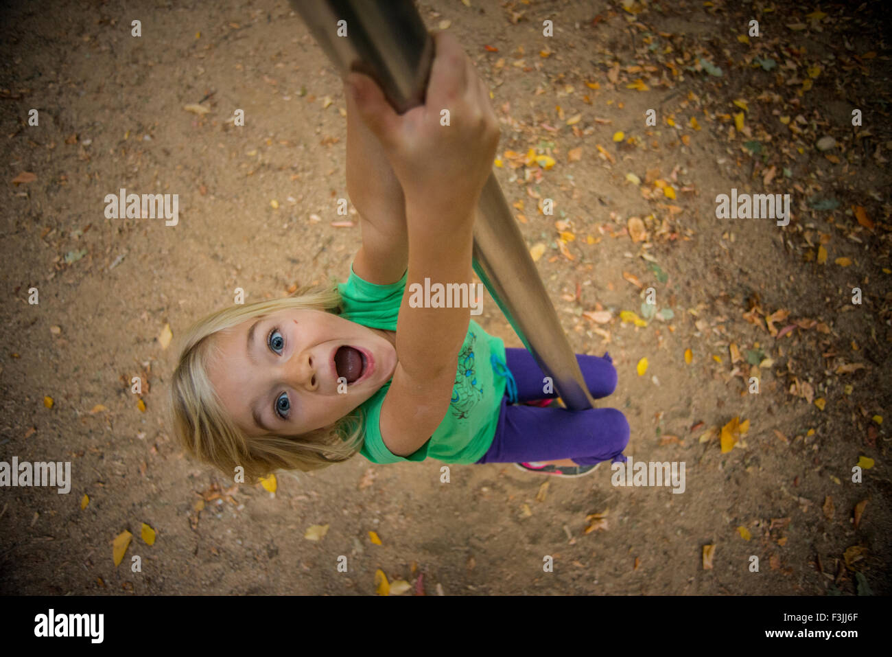 Child Girl climbs on a pole at the playground, sliding, kid playing Stock Photo