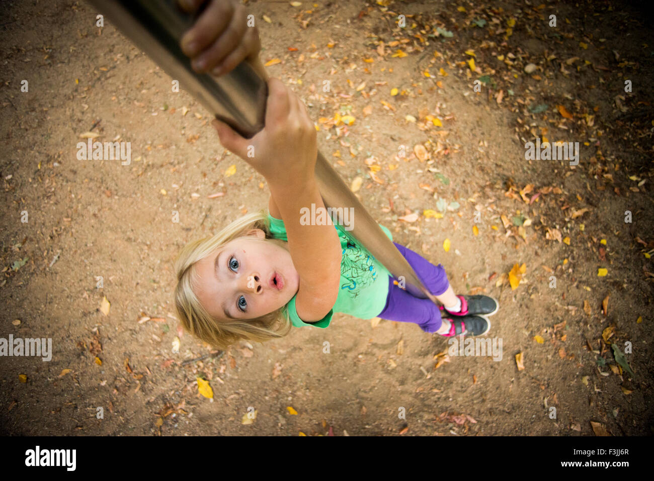 Child Girl climbs on a pole at the playground, sliding, kid playing - Stock Image
