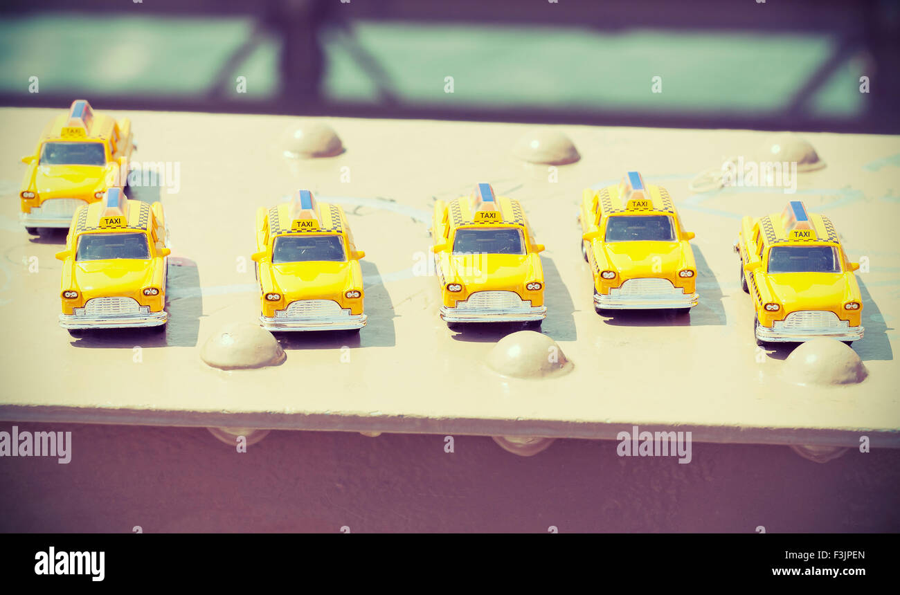 Cross processed instagram photo of taxi toys on Brooklyn Bridge, travel concept. - Stock Image