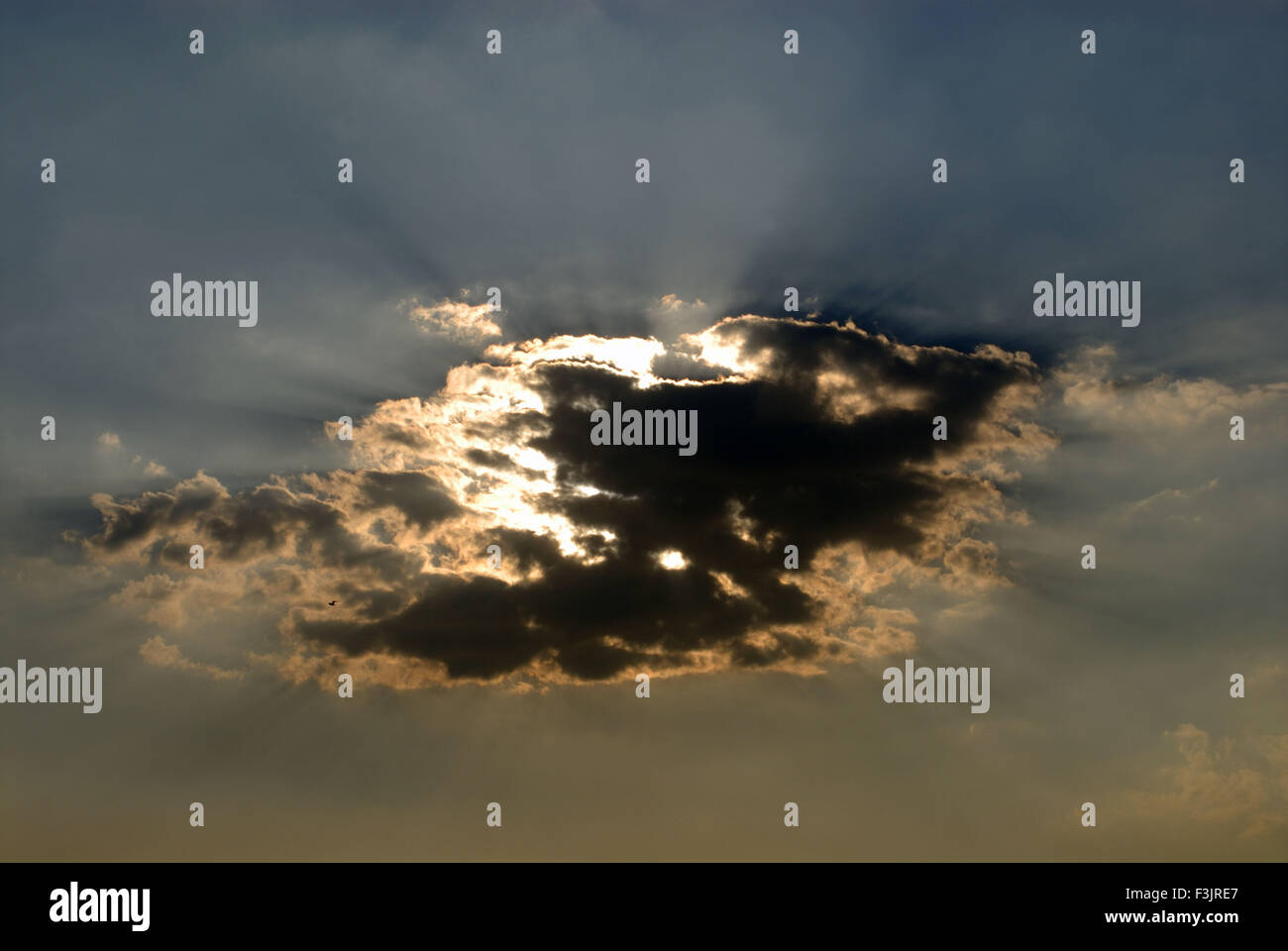 Sun behind black grey white clouds with silver lining - Stock Image