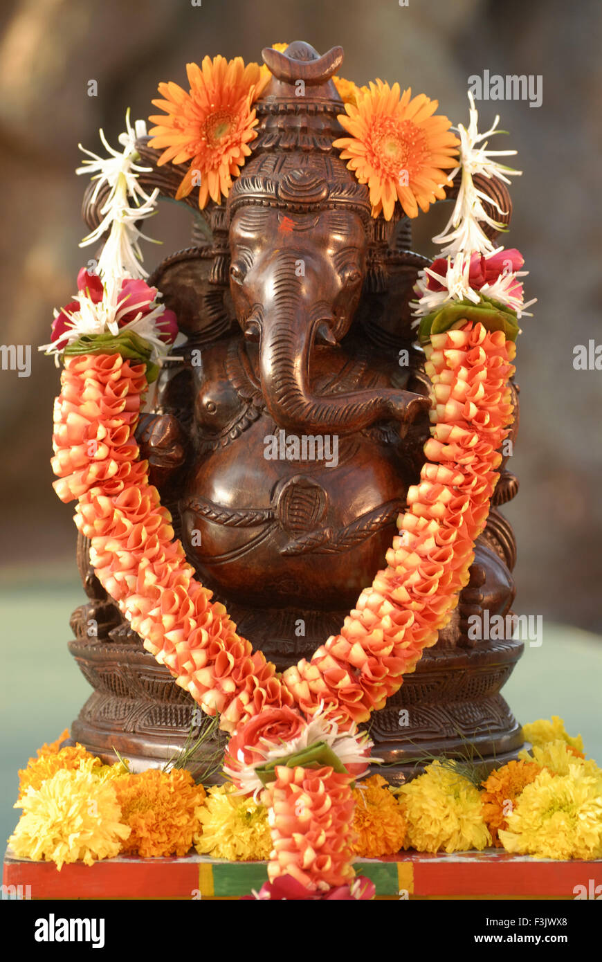 wood carved Idol Lord Ganesh painted Copper metal garlanded flowers marigold elephant headed God Ganapati Mumbai - Stock Image