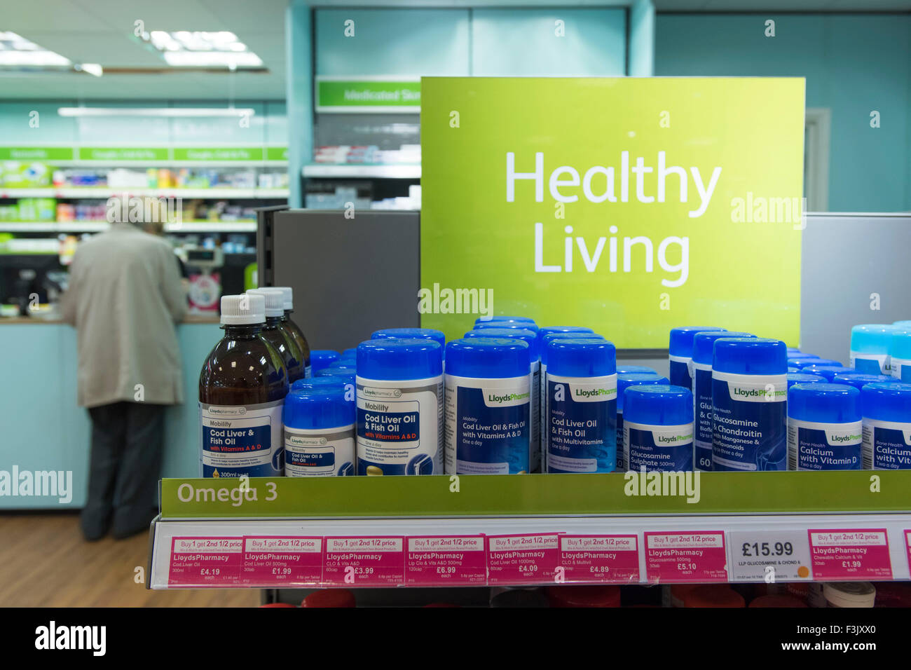 A shelf of healthy living supplements and vitamin tablets in a chemist / pharmacy. - Stock Image