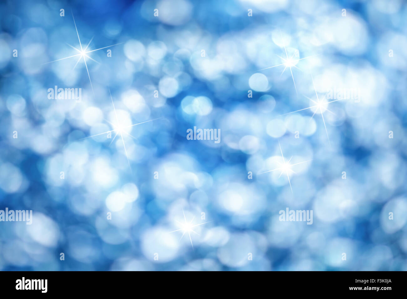 Out of focus lights creating a blue bokeh background with bright highlights, ideal for Christmas - Stock Image