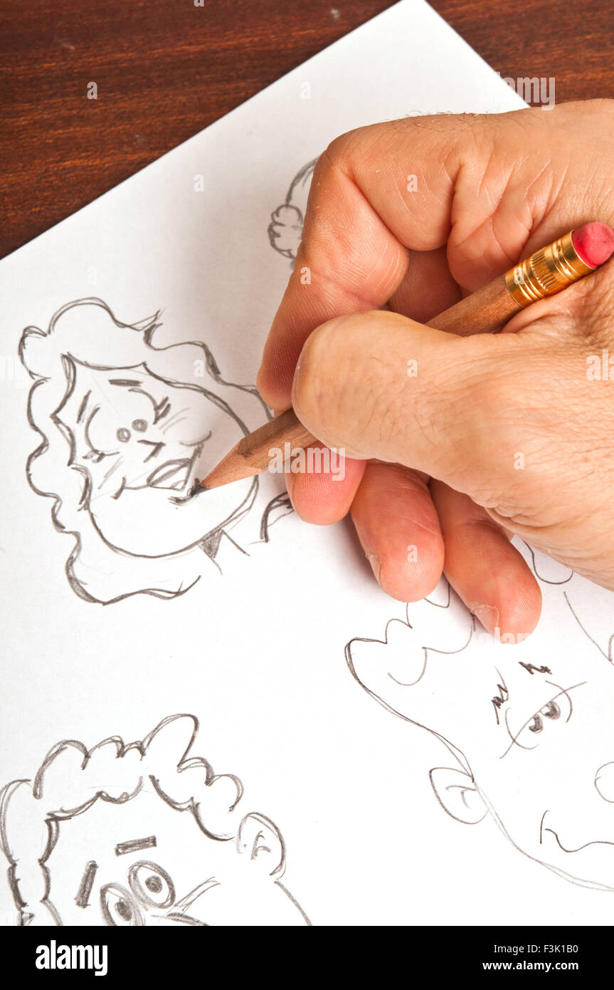male hand drawing a cartoon figure - Stock Image