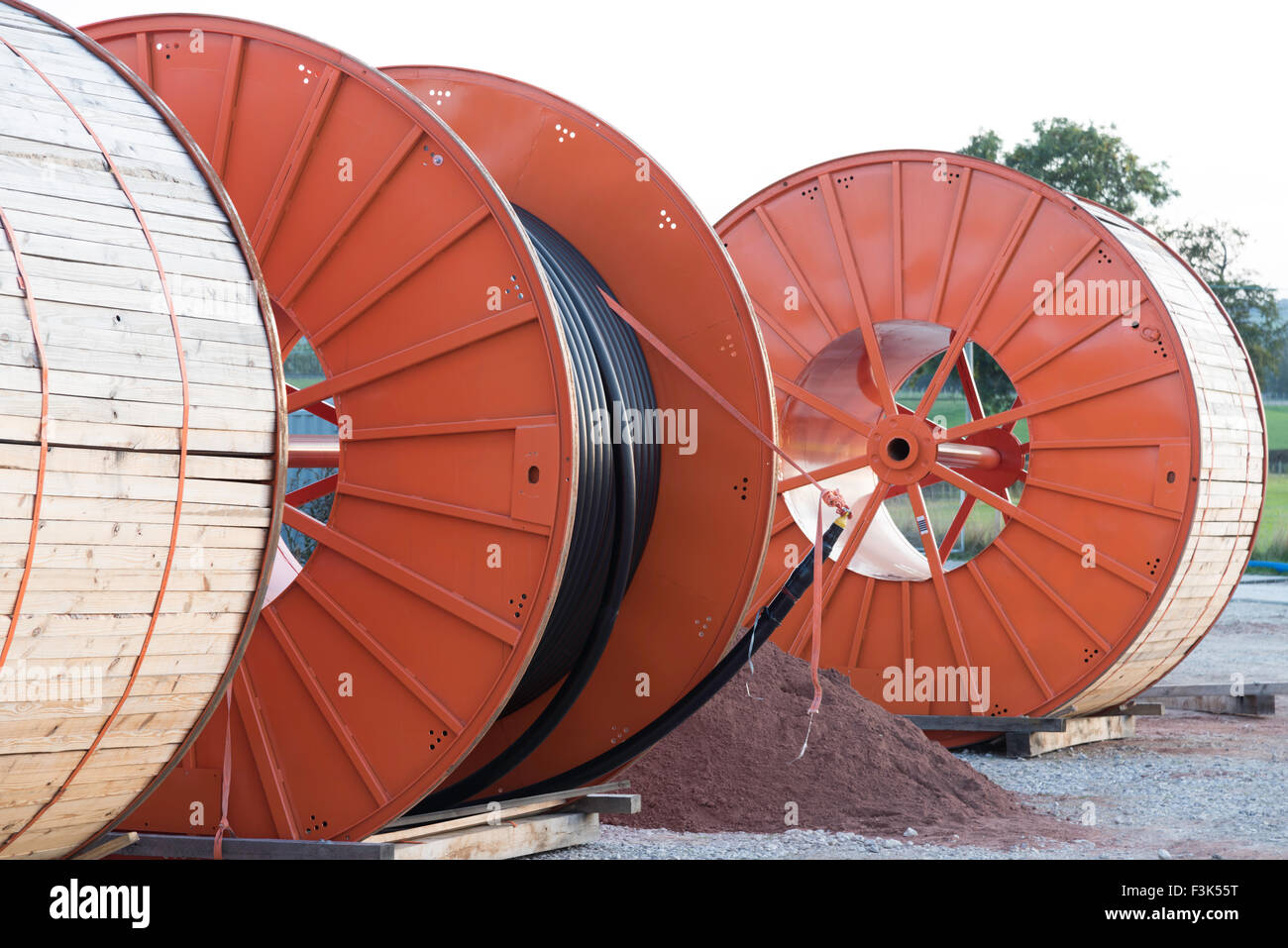 3 large orange metal and wood industrial cable drums on a site linking an offshore wind farm to the UK national - Stock Image