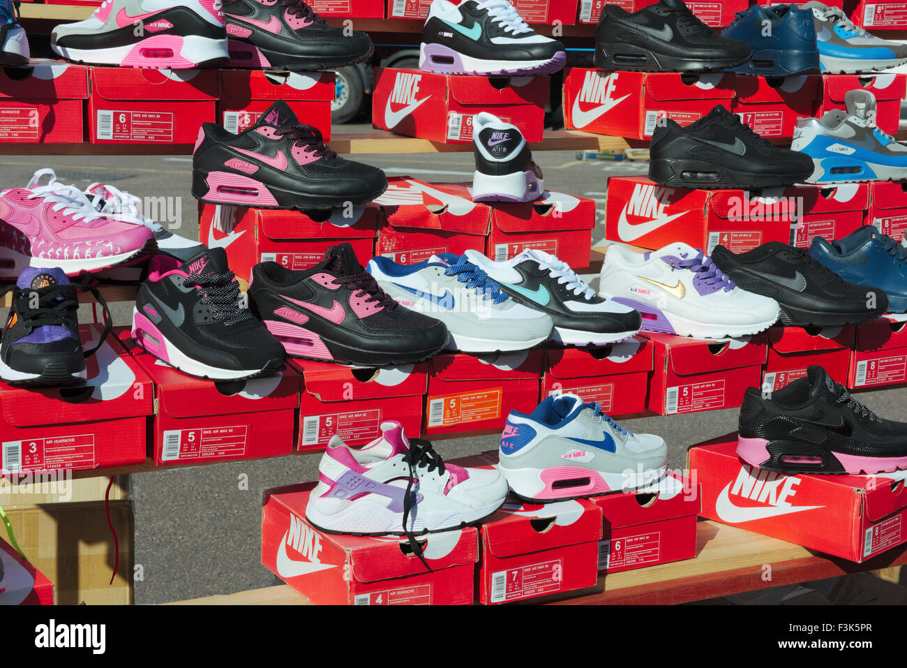Display of colourful trainers on sale in outdoor market stall - Stock Image