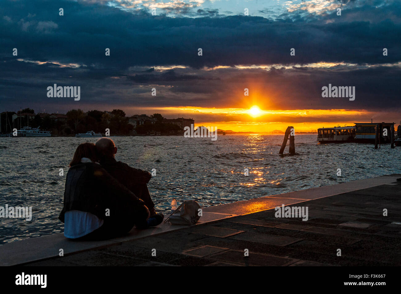 8th October 2015. San Basilio, Venice, Italy. A couple watch the sunset over Canale di Fusina. Credit:  Richard Stock Photo
