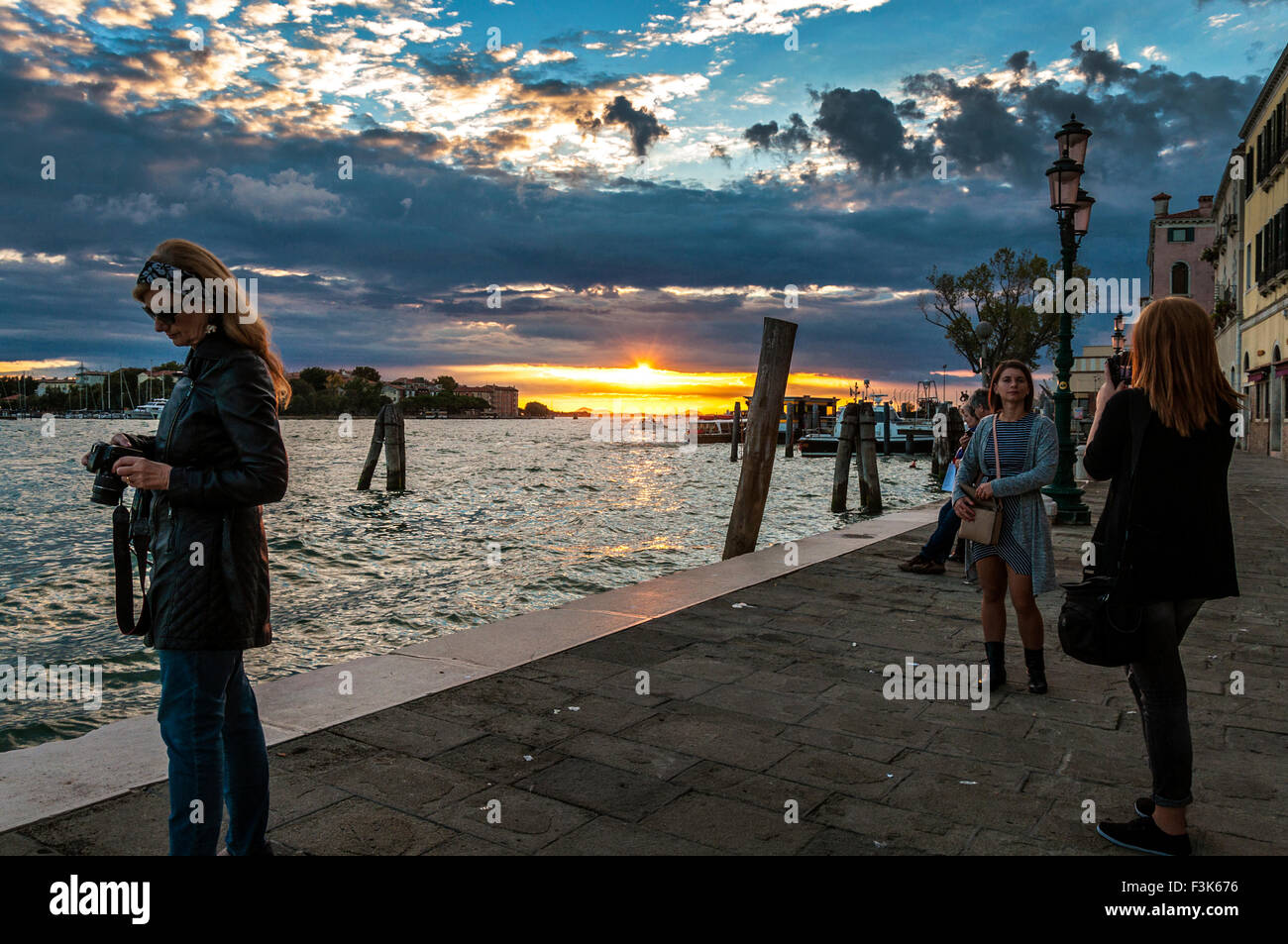 8th October 2015. San Basilio, Venice, Italy. People photograph the sunset over Canale di Fusina. Credit:  Richard Stock Photo