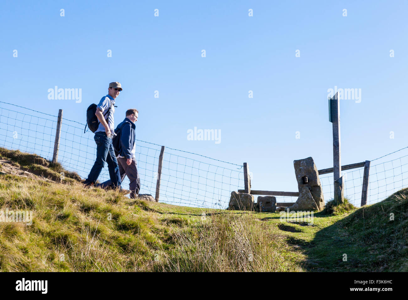 Rambling in the English countryside. Walkers approaching a stile on The Great Ridge, Derbyshire, Peak District, - Stock Image