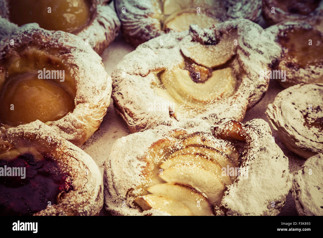 Freshly baked, lightly dusted, pastries made in a bakery in the UK - Stock Image