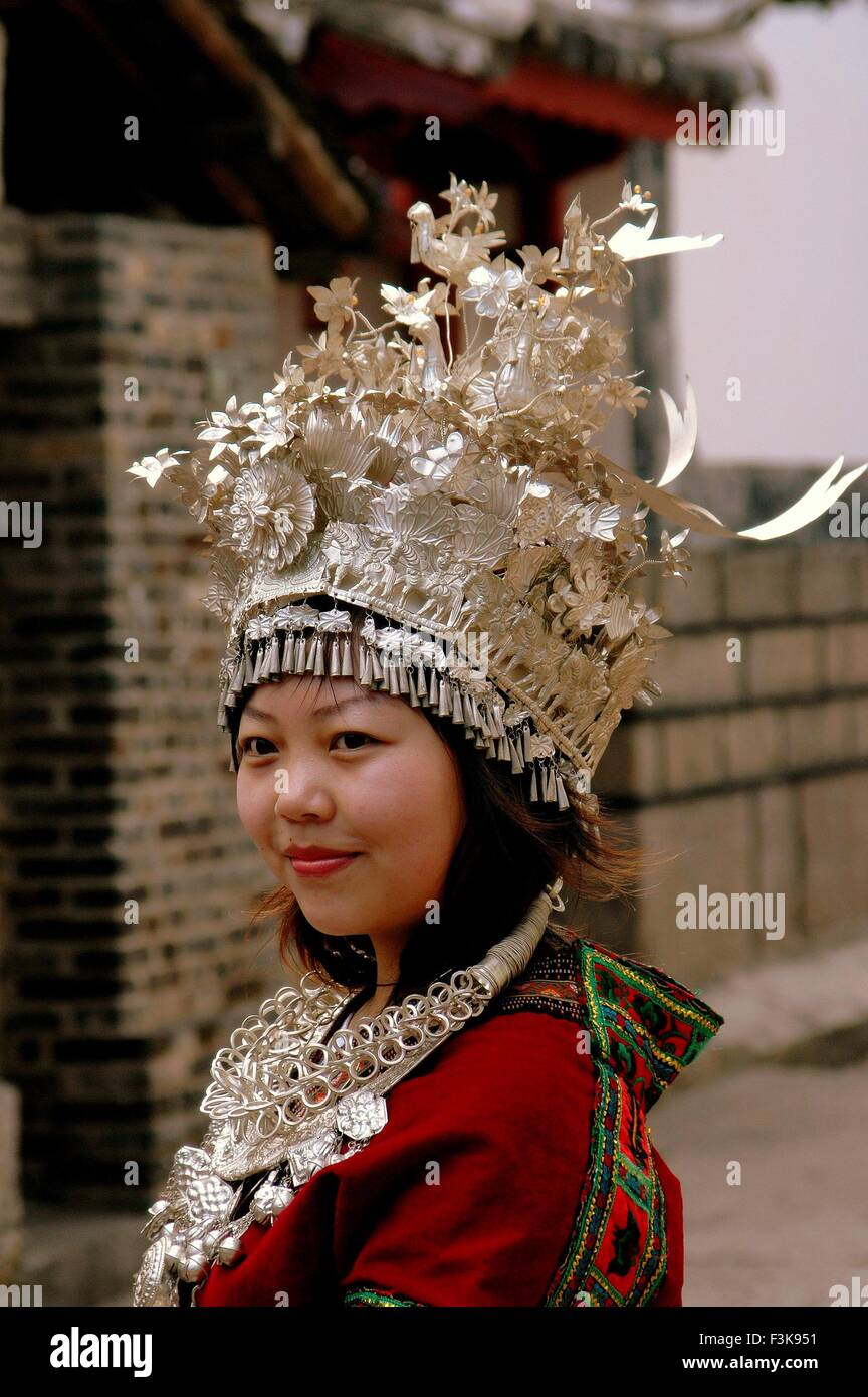 Lijiang, China:   Young Chinese woman wearing traditional Naxi clothing with ornate hand-tooled and crafted silver - Stock Image