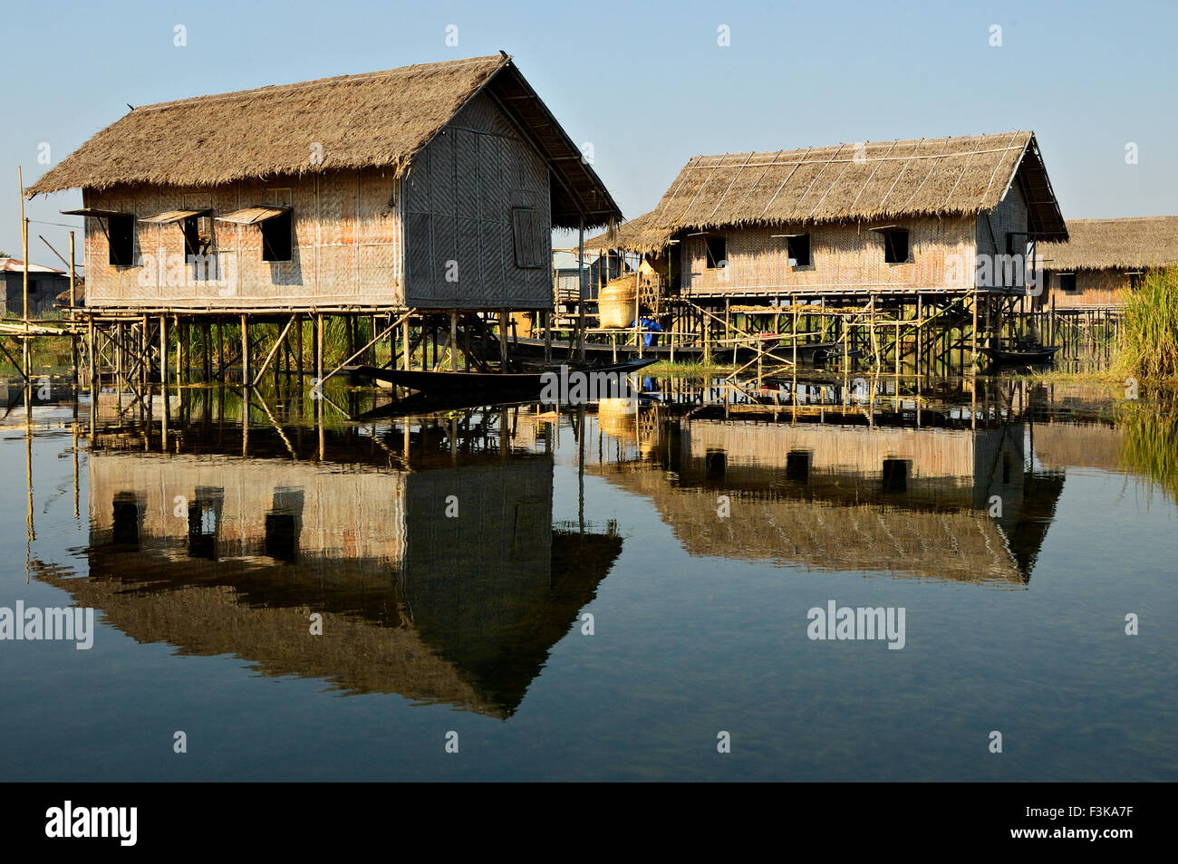 Reflection of wooden stilted houses on Inle Lake, Shan State, Myanmar - Stock Image