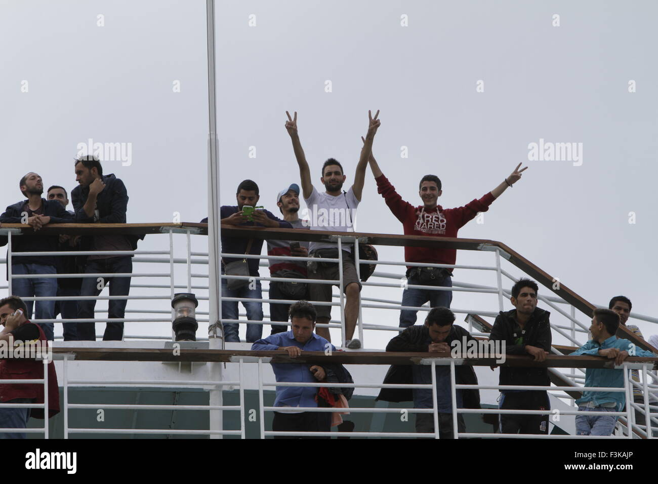 Piraeus, Greece. 08th Oct, 2015. Refugees wave from the railing of the El. Venizelos while it docks in Piraeus Harbour. - Stock Image