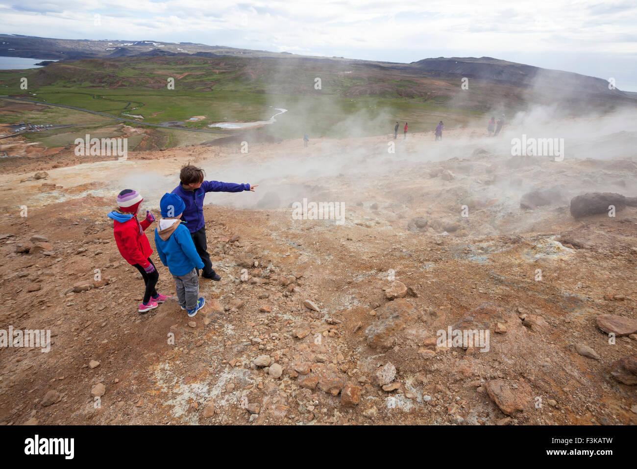 Visitors beside steaming volcanic vents at Seltun, Krysuvik geothermal area, Reykjanes Peninsula, Iceland. - Stock Image