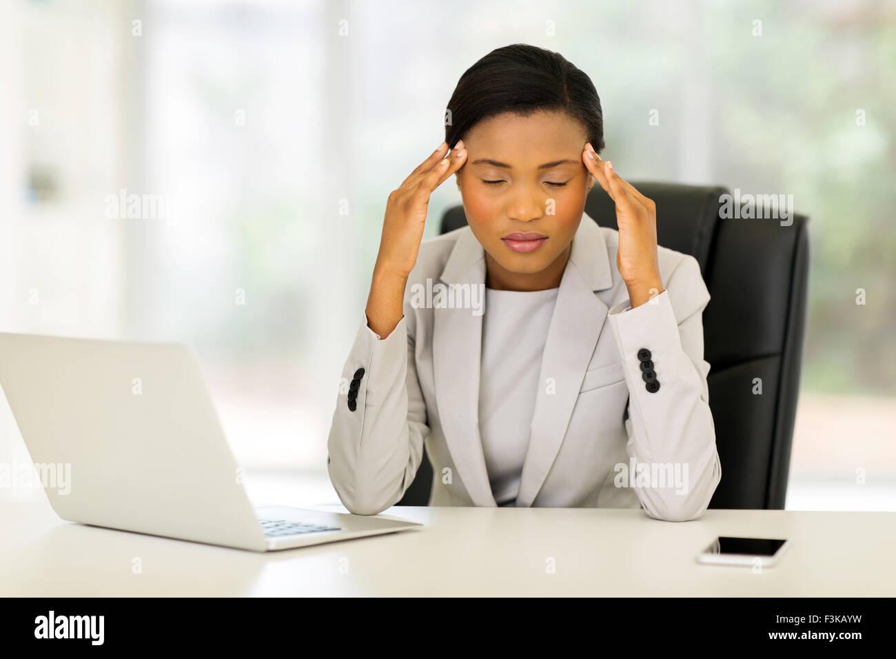 overworked African American businesswoman having headache - Stock Image
