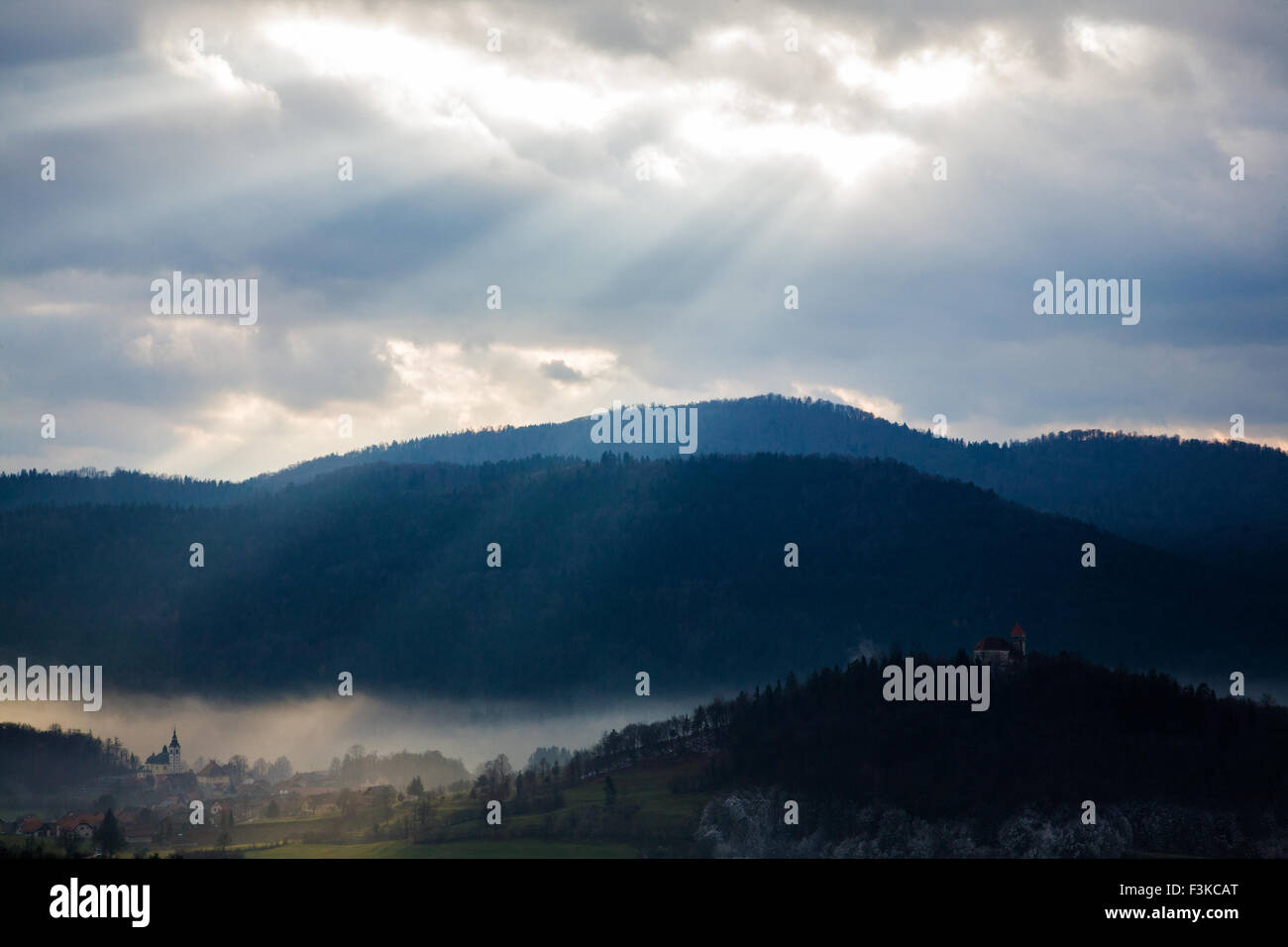 Afternoon sunrays falling over the church of Saint Vitus in Preserje, Slovenia. You can also see the church of Sveti - Stock Image