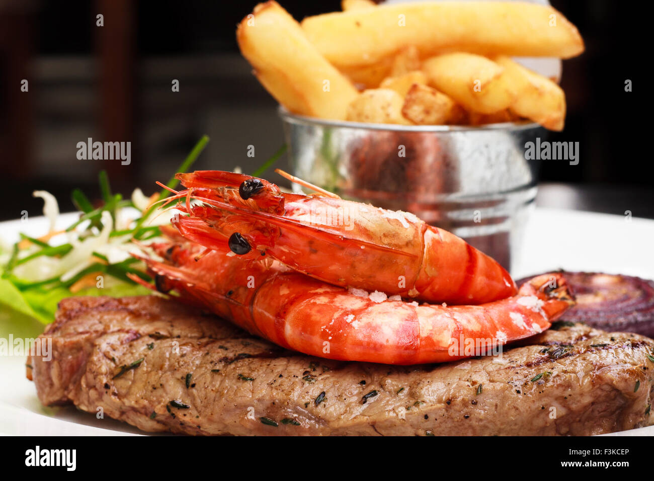 Surf and turf ( Steak and King Prawn served with fries and Asian slaw) - Stock Image