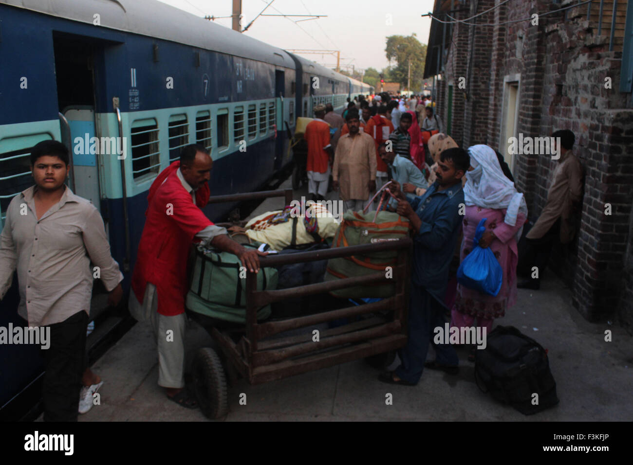 Lahore, Pakistan. 08th Oct, 2015. Passengers of Samjhuata express carry their luggage upon arriving in Lahore railway Stock Photo