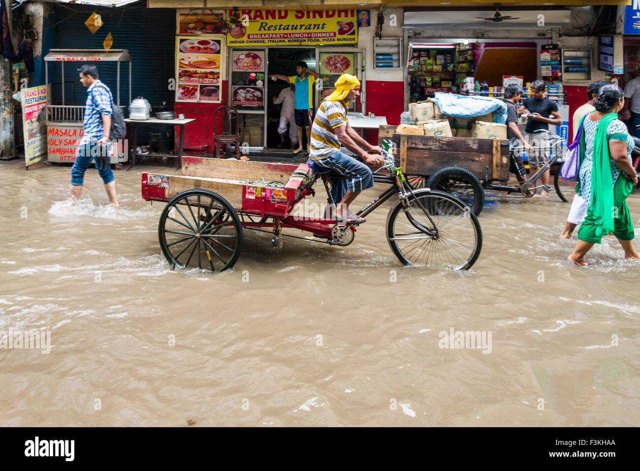 A cycle rikshaw is moving through the flooded streets of the suburb Paharganj after a heavy monsoon rainfall Stock Photo