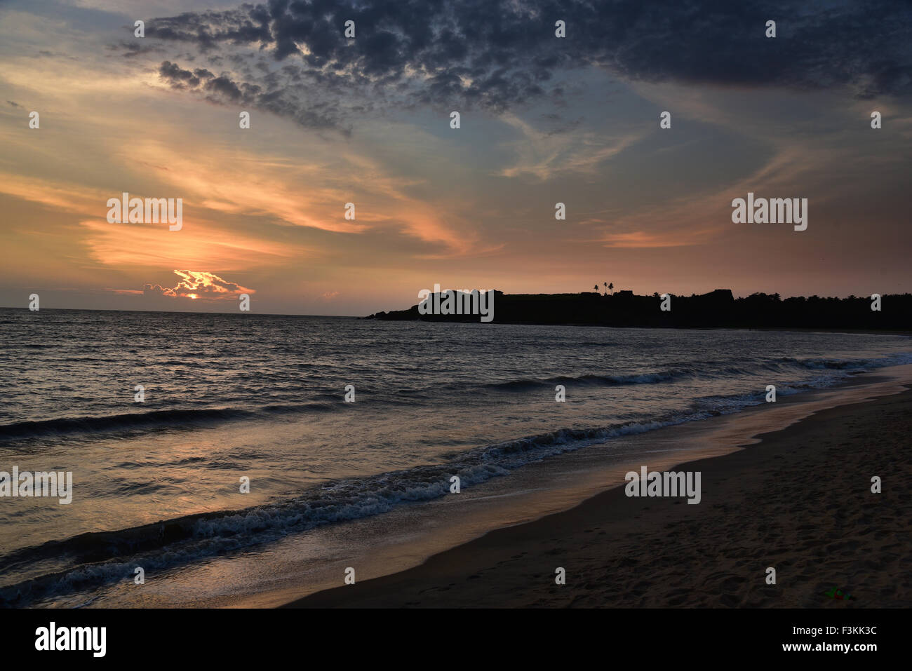 Sunset over ocean and beach in Kerala India.Bekal fort beach Kasargode.Beach,cloud,flat,horizon,india,indian,kerala,ocean,reflec - Stock Image