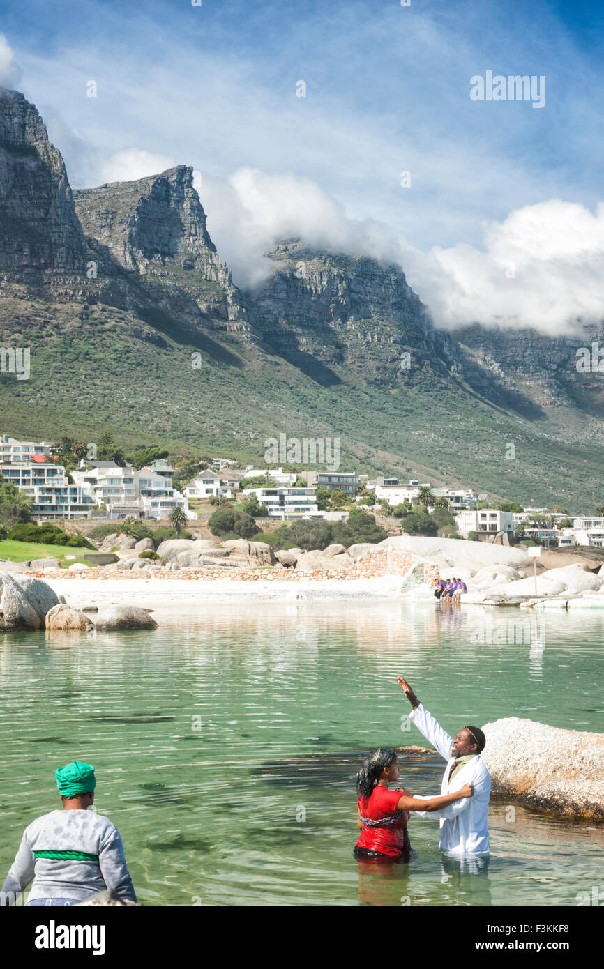 Sangoma healer performing a water baptism in the Atlantic Ocean, Table Mountain's Twelve Apostles in background, - Stock Image