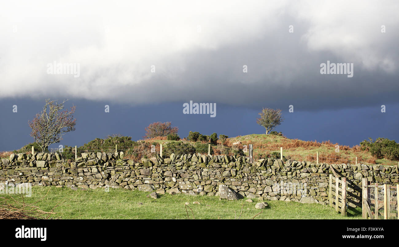 A farmers land, Sun is shining whilst the overcast weather is getting closer - Stock Image