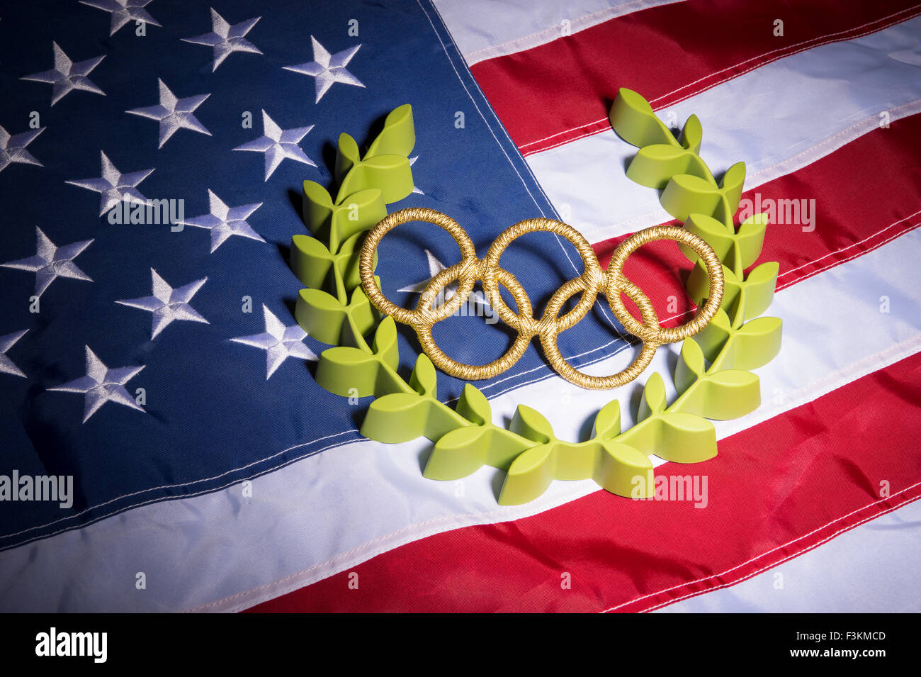 RIO DE JANEIRO, BRAZIL - FEBRUARY 3, 2015: Gold Olympic rings rest with laurel wreath on American flag background. - Stock Image