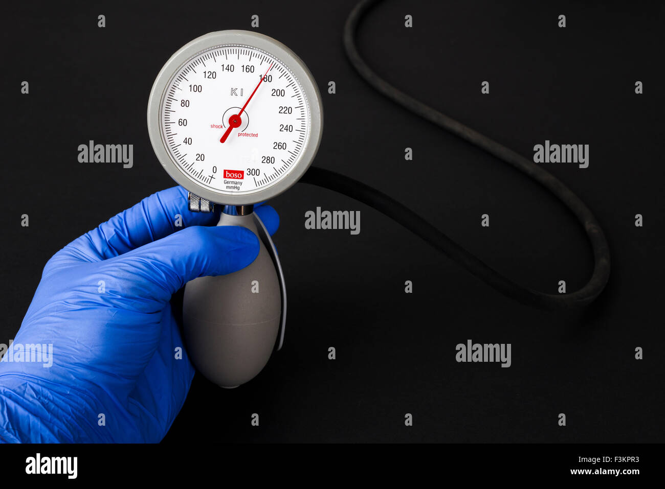 A hand in a blue medical glove is holding a sphygomanometer, blood pressure meter, for medical use, indicating high - Stock Image