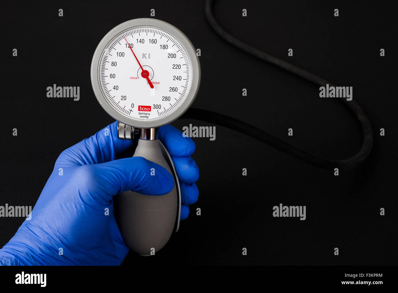 A hand in a blue medical glove is holding a sphygomanometer, blood pressure meter, for medical use, indicating normal - Stock Image