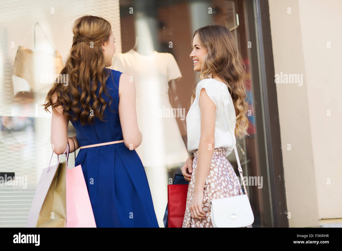 happy women with shopping bags at shop window - Stock Image