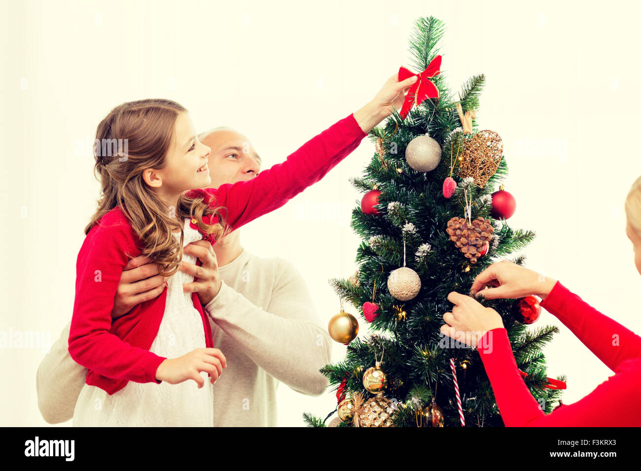 smiling family decorating christmas tree at home - Stock Image