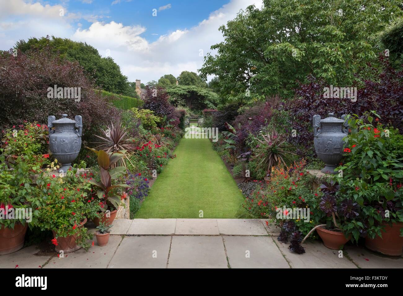 English garden borders with steps, urns and lawn. - Stock Image