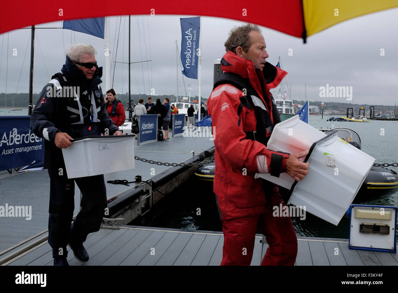 Cowes Week, 2015, Isle of Wight committee members carrying equipment off boats Yacht Racing, Shore side entertainments, - Stock Image