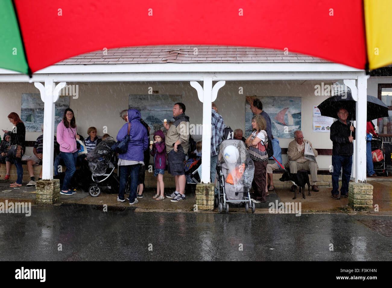 Cowes Week, 2015, Isle of Wight people sheltering from the rain The Parade RNLI Yacht Racing, Shore side entertainments, - Stock Image