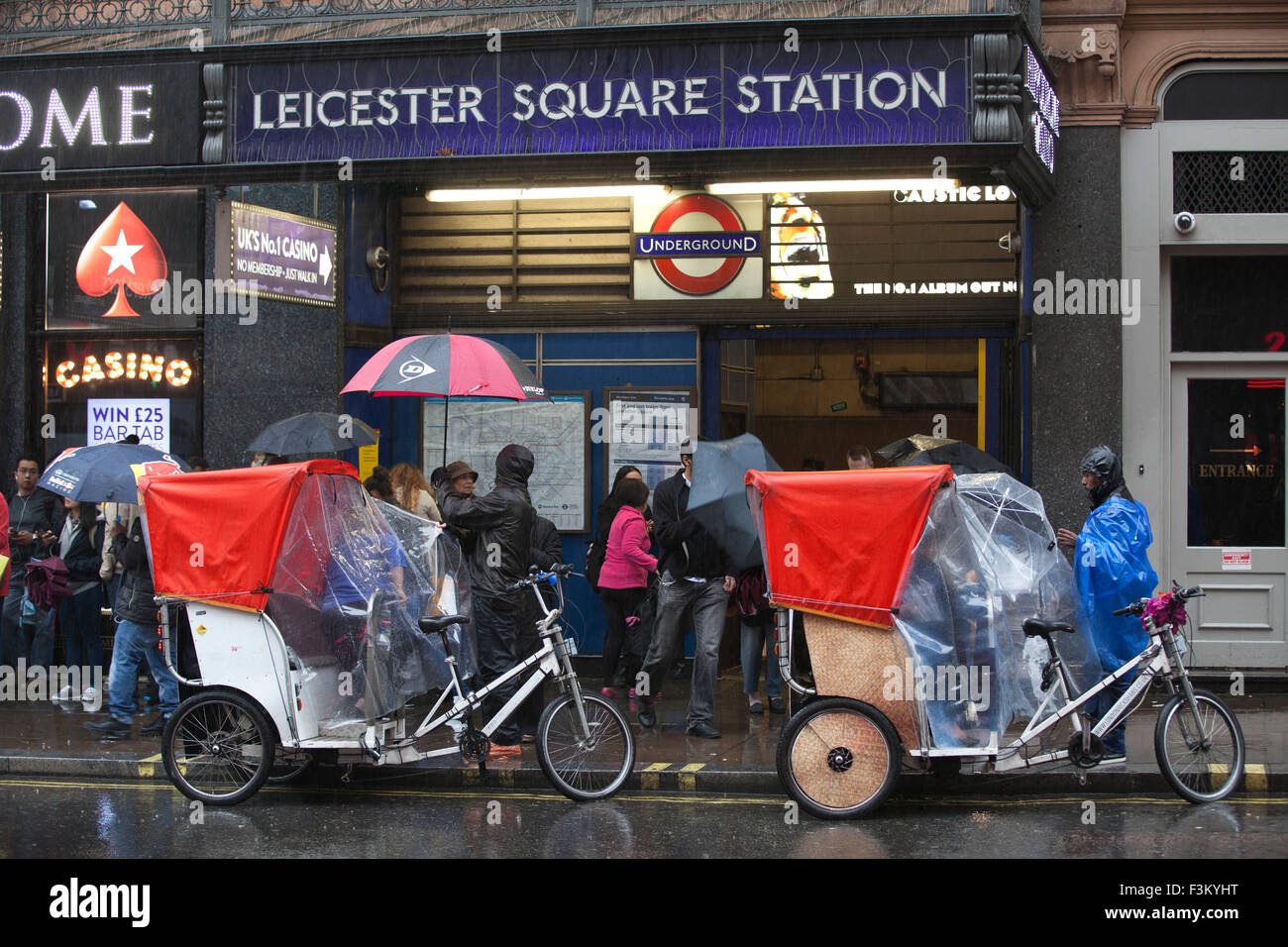 London rickshaw drivers wait outside Leicester Square Underground station for commuters on a wet day, London, England, - Stock Image