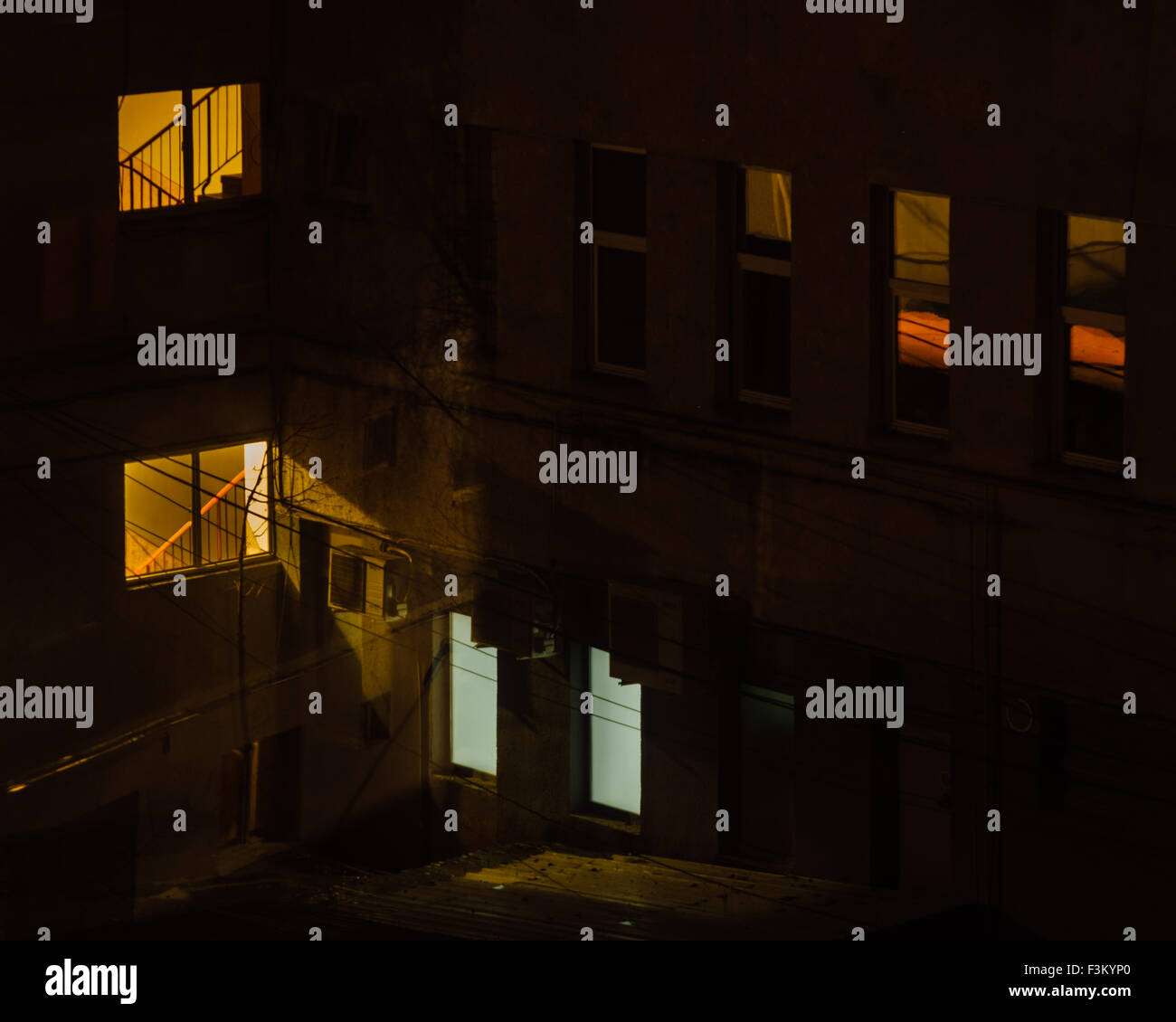 Apartments, windows, lights, concrete blocks in the night in Romania, panel houses constructed in communism. Urban Stock Photo