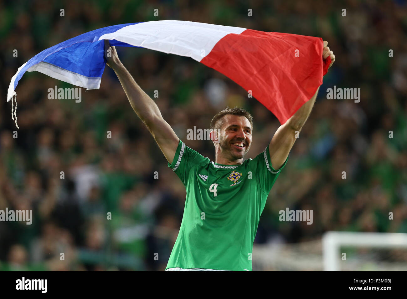 Belfast, UK. 8th October, 2015.Gareth McAuley of Northern Ireland celebrates with a French flag at the end of theStock Photo