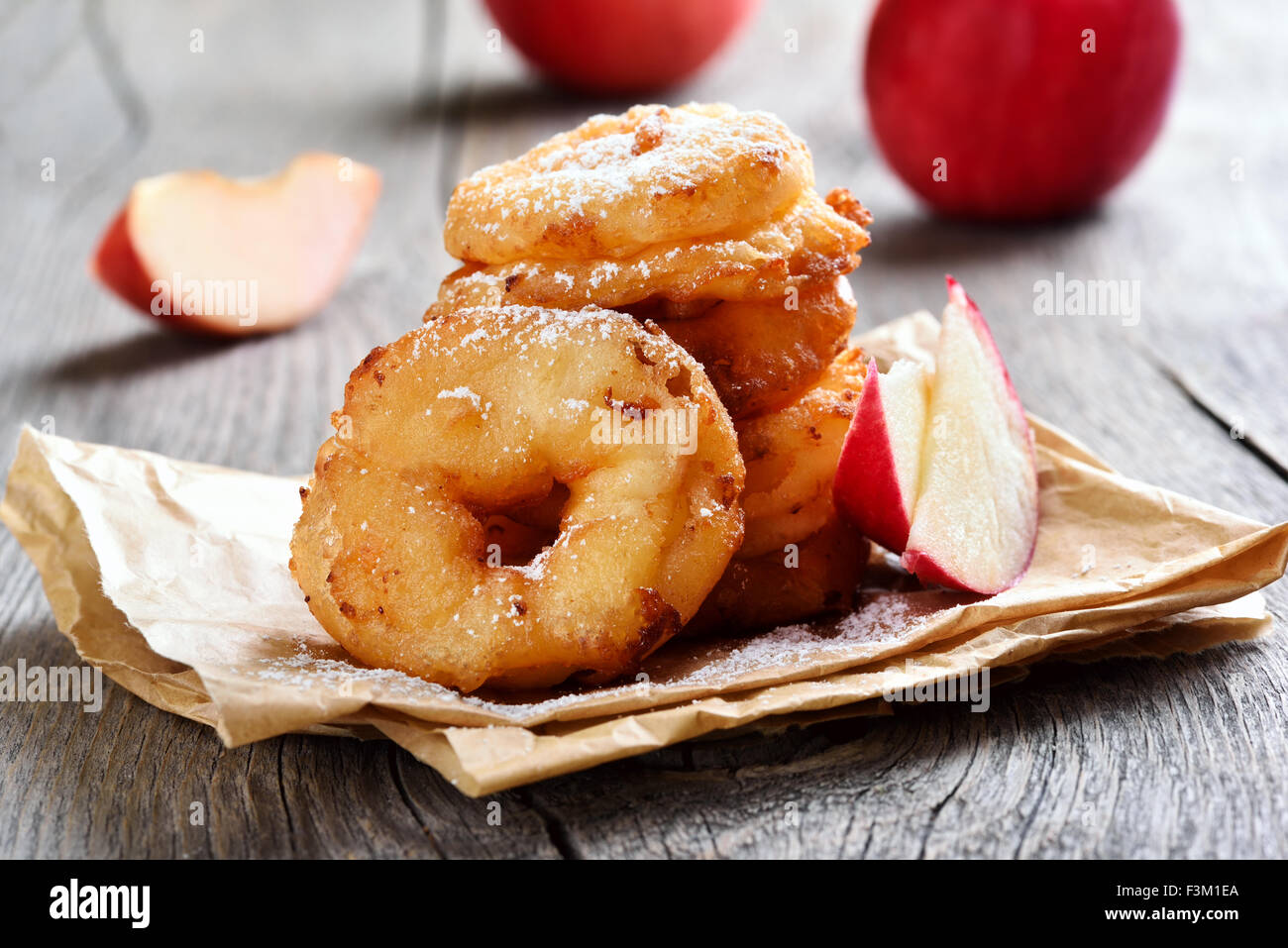Apple rings over baking paper on rustic table - Stock Image
