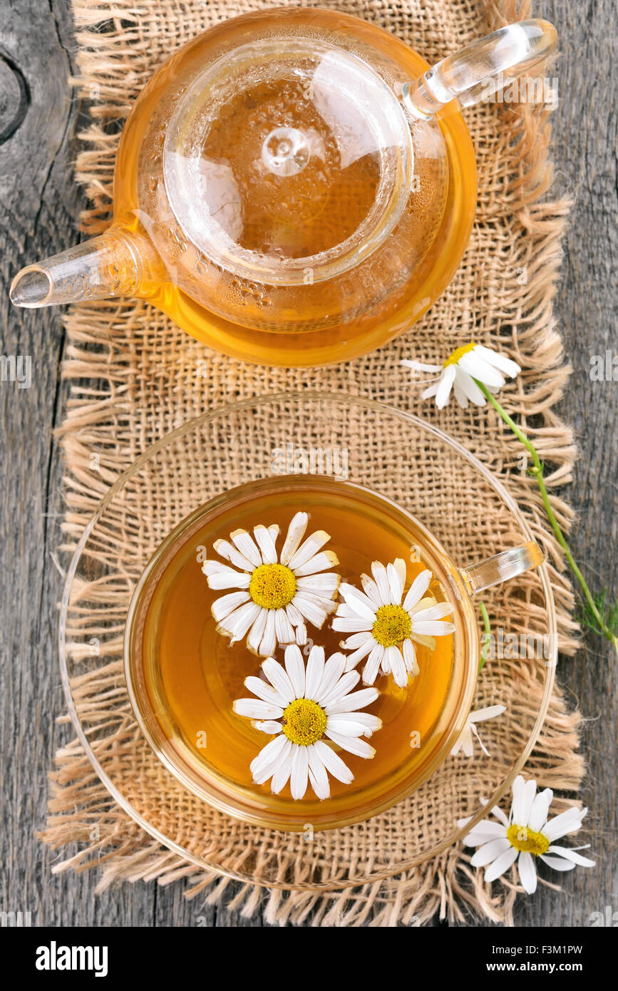 Chamomile tea and teapot on wooden table, top view - Stock Image