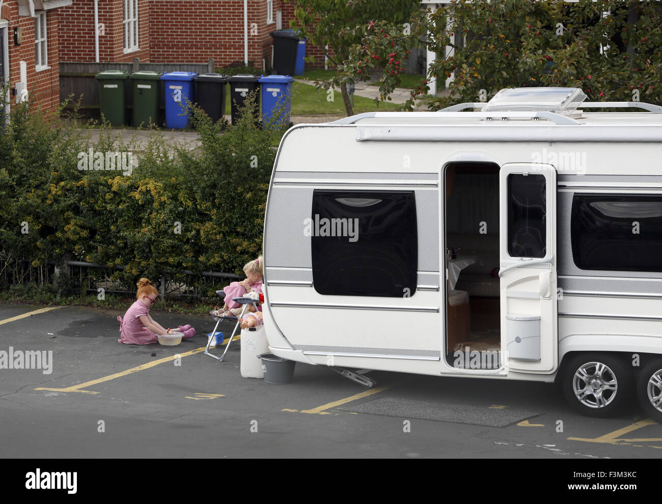 Travellers children play outside their caravan. - Stock Image