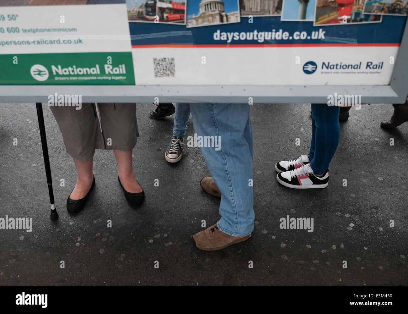 National rail people on train platform waiting - Stock Image