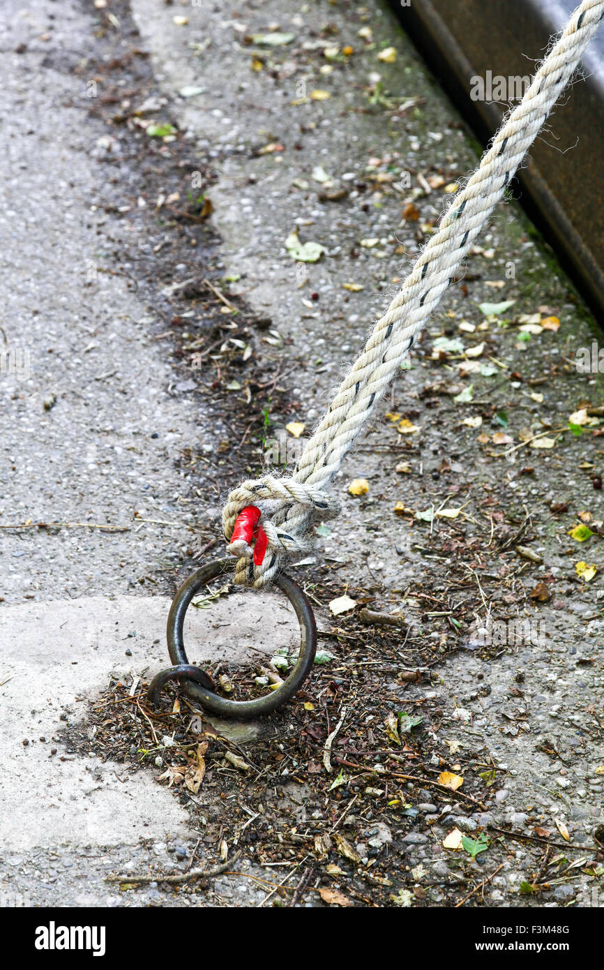 A rope tied to a mooring ring by the side of a canal - Stock Image