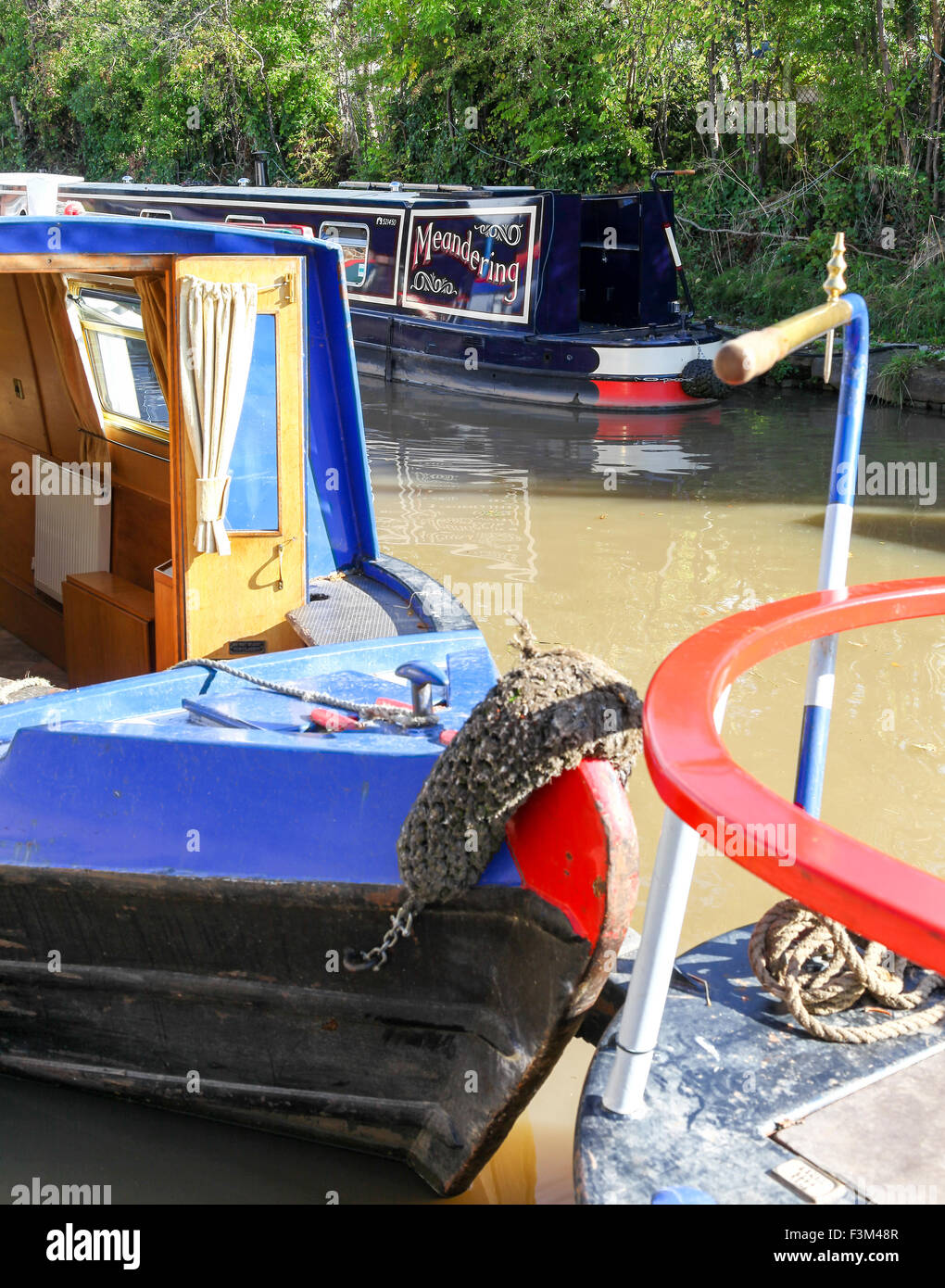 The front of two narrowboats or canal boats one named Meandering on the Shropshire Union Canal at Middlewich Cheshire - Stock Image