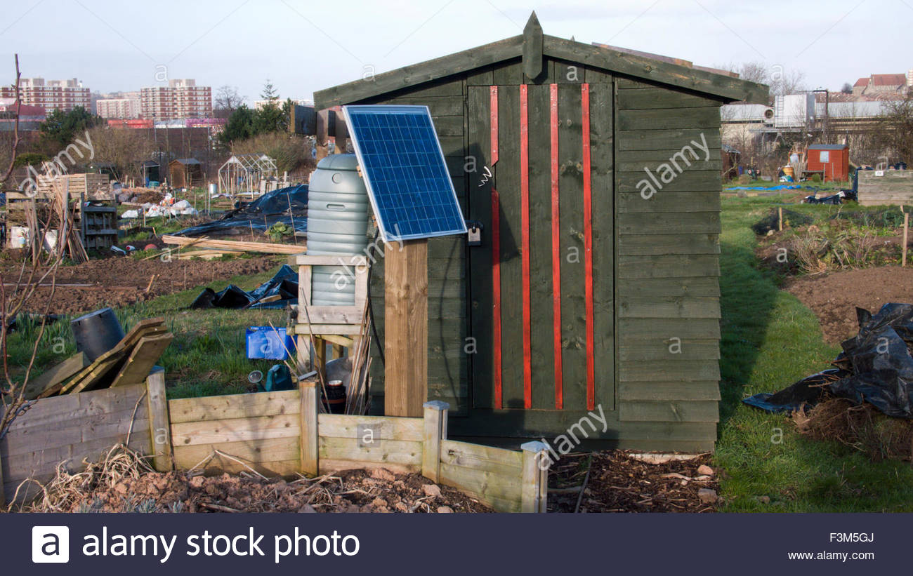 Garden shed on allotment with solar panel to power rabbit proof fence - Stock Image