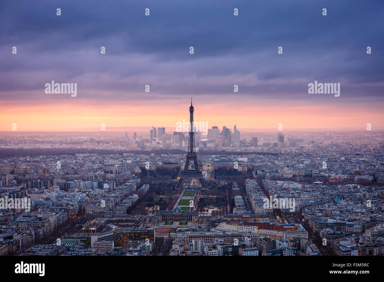 Paris cityscape clad in pink at dusk. Aerial view of Paris and the Eiffel Tower, Champ de Mars, Trocadero and La - Stock Image