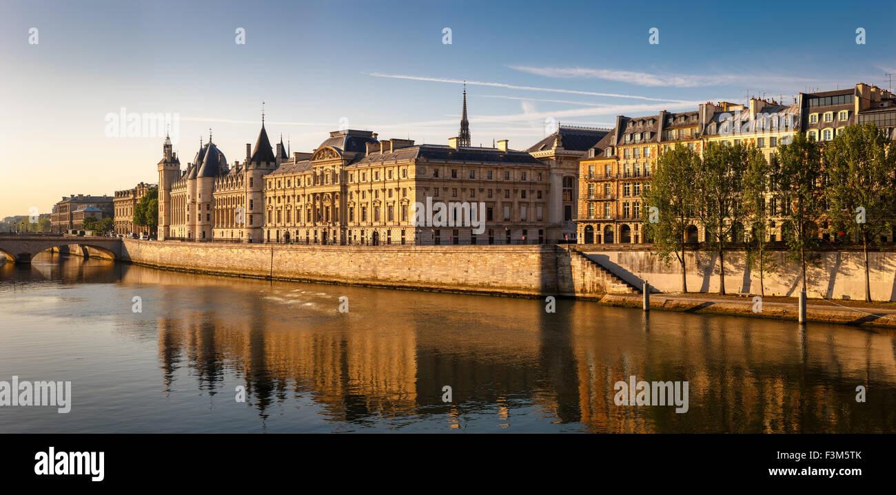 River Seine right bank with glowing morning light showcasing the Conciergerie, Quai de l'Horloge on Ile de la - Stock Image