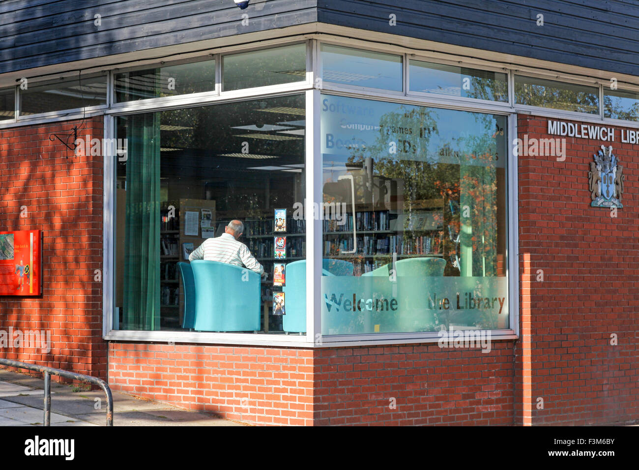 A man reading sitting in the window of Middlewich library Middlewich Cheshire - Stock Image