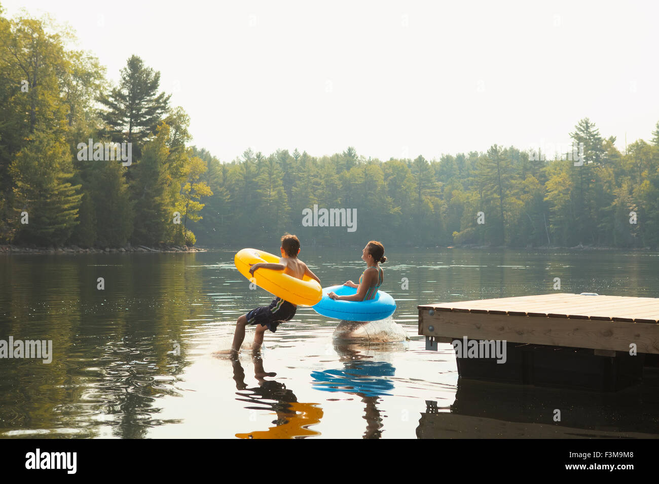 Girl,Jetty,Jumping,Ring,Inflatable,Boy,Lake - Stock Image