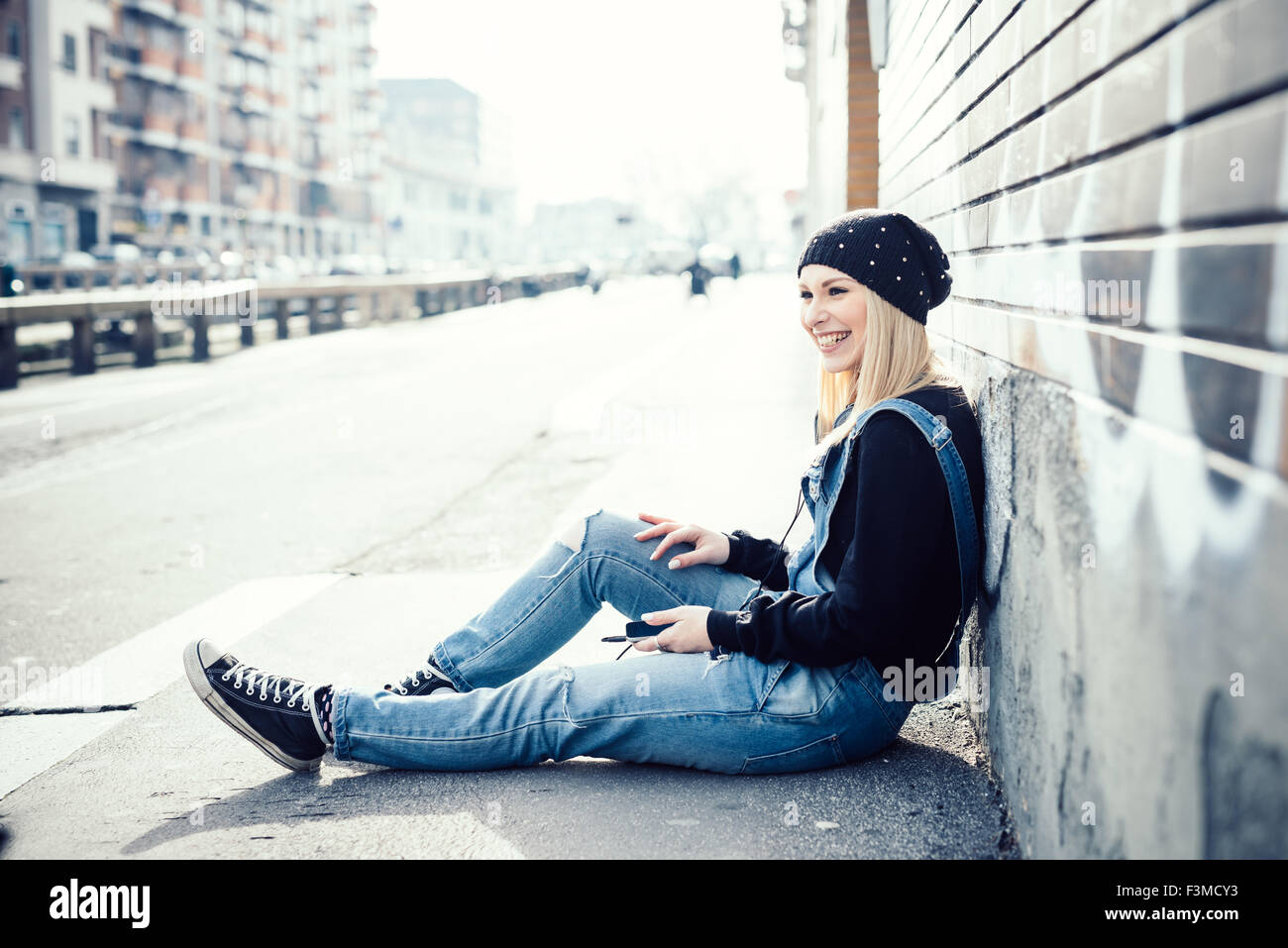 young beautiful blonde straight hair woman in the city, sitting on the ground, overlooking right, holding a smartphone, - Stock Image