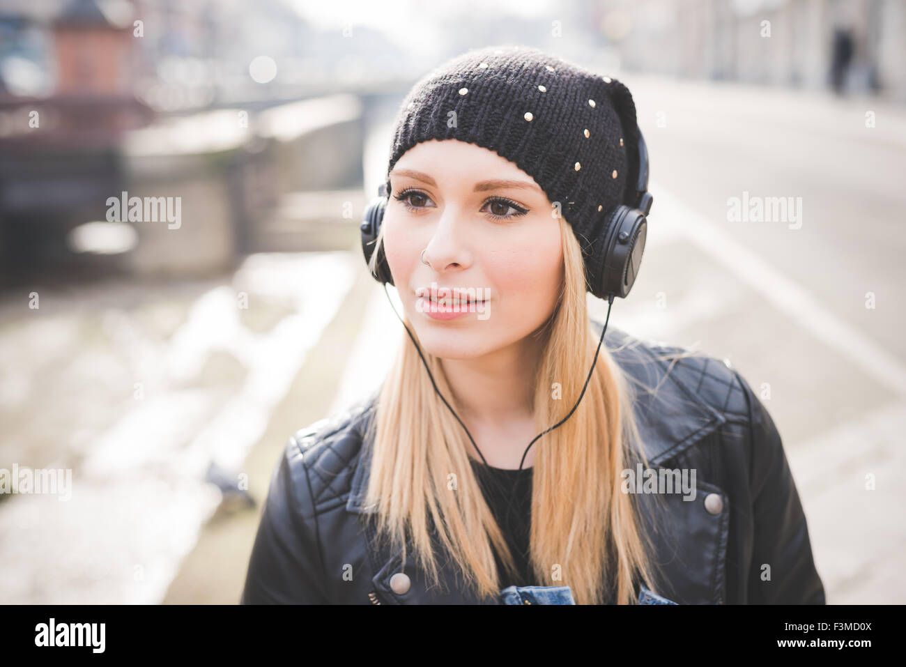 Portrait of young beautiful blonde straight hair woman in the city with headphones listening to music, overlooking - Stock Image